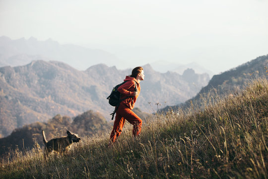 Beautiful woman traveler climbs uphill with a dog on a background of mountain views. She is with a backpack and in red clothes.