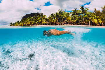 Young attractive woman swimming underwater in transparent ocean. Mauritius, Le Morne