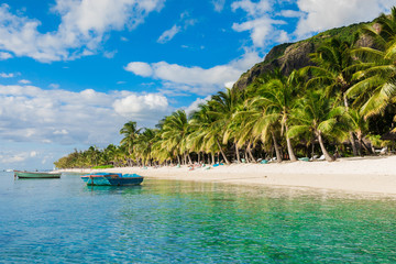 Tropical view of the resort on Mauritius. Ocean with boat, sandy beach with palms