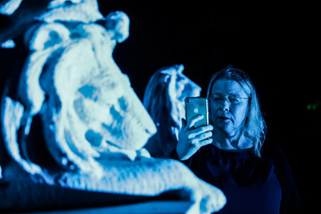 A tourist takes a picture of a statue of a lion during the Moonlight Mausoleum tour at Woodlawn Cemetery in Bronx