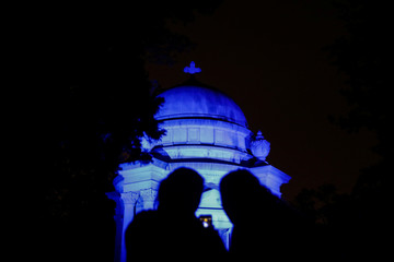 Tourists take a picture at the Coster family mausoleum during the Moonlight Mausoleum tour at Woodlawn Cemetery in Bronx in New York City