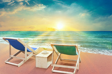 Spoed Fotobehang Olijf two beach chairs on sunset time and scenery sea view with beautiful sun rays , summer concept