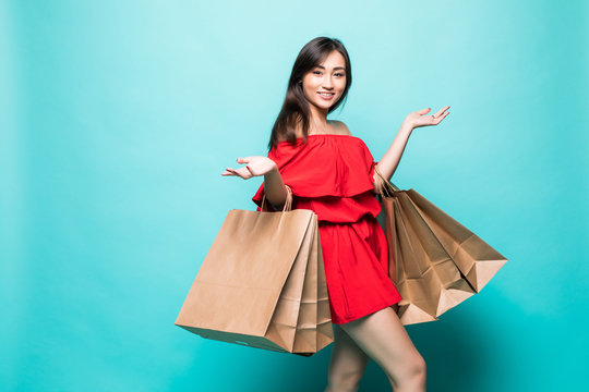 Happy shopping woman of Asian holding bags, isolated on green background.