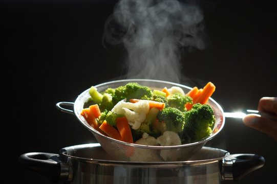 steaming of hot boiled vegetables. Basket of vegetables that just boiled from hot water with steam selective focus, soft focus. hot food, diet and healthy concept.