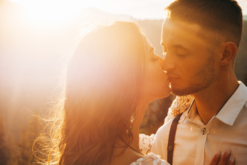 Sweet groom and the bride at boho style posing and kissing at sunset of the mountains