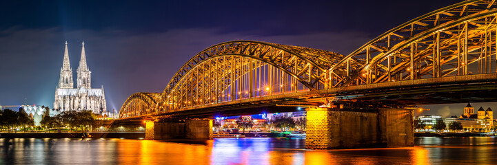 Zelfklevend Fotobehang Bruggen Panorama of the Hohenzollern Bridge over the Rhine River and Cologne Cathedral by night