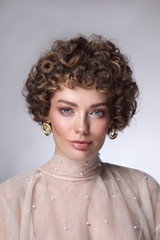 Vintage style portrait of young beautiful woman with curly hair and natural makeup
