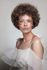 Vintage style portrait of young beautiful woman with curly hair and fancy makeup
