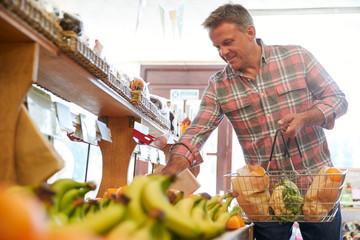 Male Customer With Shopping Basket Buying Fresh Produce In Organic Farm Shop