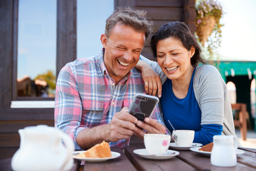 Mature Couple In Garden Center Cafe Looking At Pictures On Mobile Phone