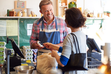 Customer At Checkout Of Organic Farm Shop Making Contactless Payment