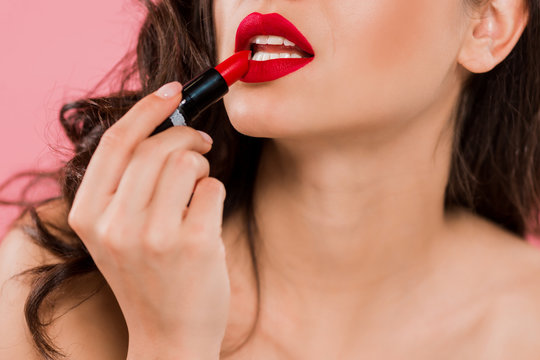 cropped view of woman applying lipstick on red lips isolated on pink