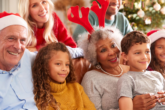 Multi-Generation Family Sitting On Sofa At Christmas Watching Television Together