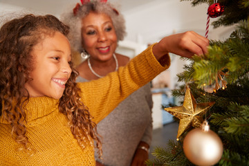 Grandmother And Granddaughter Decorating Christmas Tree At Home Together