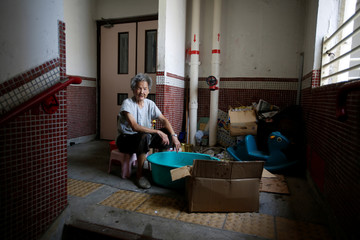 An old woman washes aluminium cans and bottles in a small bath in a stairwell in Lung Hing building to sell to recyclers at Wong Tai Sin, in Hong Kong