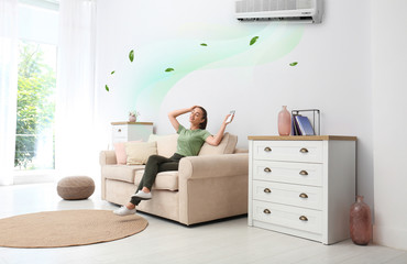 Fototapeta Happy young woman switching on air conditioner with remote control at home