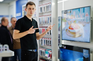 Seller man professional consultant in tech store or shop stand near smart TV.