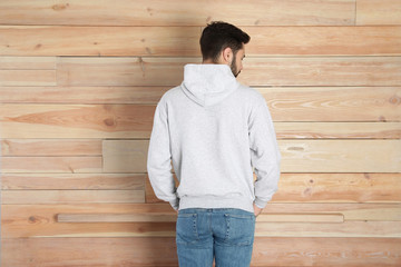 Wall Mural - Young man in sweater at wooden wall. Mock up for design