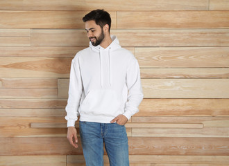 Wall Mural - Portrait of young man in sweater at wooden wall. Mock up for design