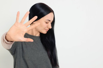 Young woman making stop gesture against white background, focus on hand. Space for text