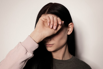 Young woman covering face against light background