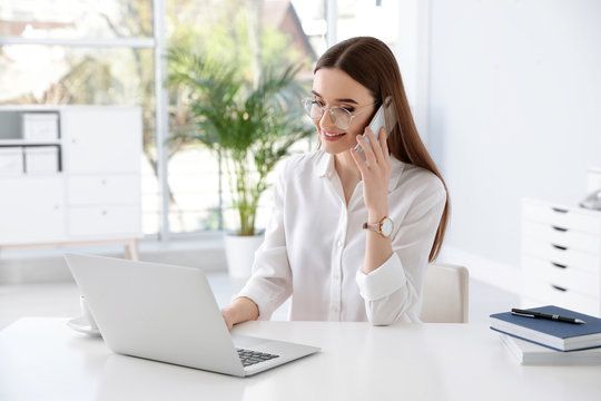 Young businesswoman talking on phone while using laptop at table in office