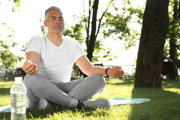 Handsome mature man practicing yoga in park, space for text. Healthy lifestyle