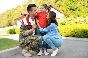 Man in military uniform and his family outdoors