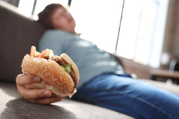 Overweight boy with burger sleeping on sofa at home