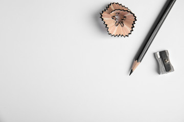 Pencil, sharpener and shaving on white background, top view