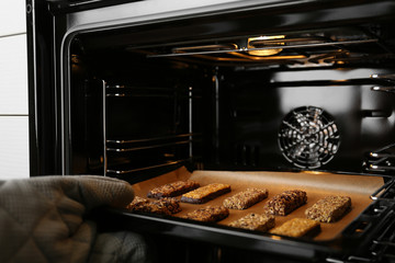 Woman taking delicious healthy granola bars from oven, closeup