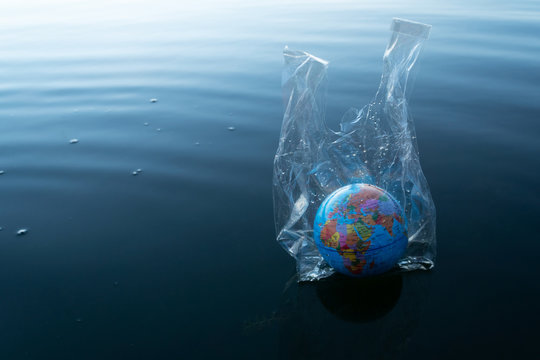 the world or earth model in a transparency plastic bag floating in dark blue ocean water for environmental pollution planet protection concept
