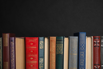 Stack of hardcover books on black background. Space for text