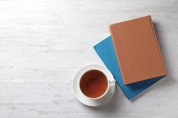Hardcover books and cup of tea on white wooden table, flat lay. Space for text
