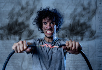Funny image of man getting electric shock with funny face and smoke all around. DIY concept