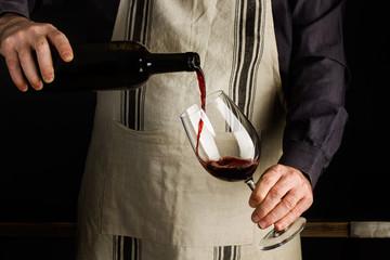 Camarero vertiendo vino tinto en copa de vino. Sommelier vierte bebida alcohólica