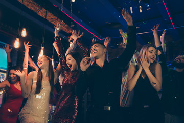 Photo of crazy chilling students dressed in formalwear putting their hands up rejoicing with party started faces with smile screaming shouting with happiness enjoying free time