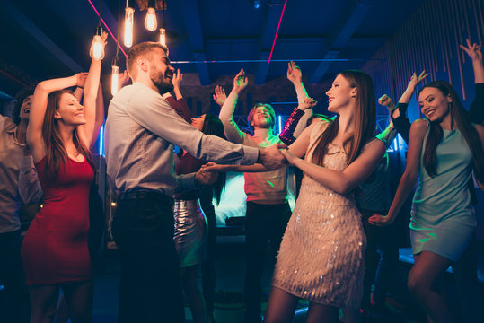 Lets dance my love. Portrait of positive cheerful couple students have wedding party dance on discotheque with lots people crowd wearing formalwear dress skirt in spotlight