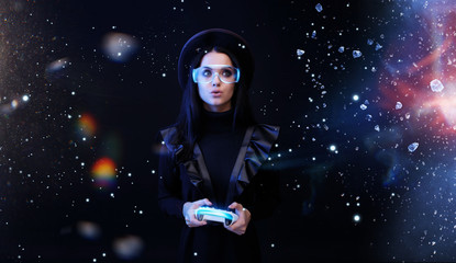 Wall Mural - Beautiful woman with joystick in glasses of virtual reality on dark magic background. Augmented reality, future technology concept. VR. Futuristic 3d glasses with virtual projection. Blue neon light.