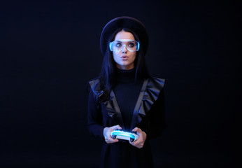 Wall Mural - Beautiful woman with joystick in glasses of virtual reality on dark background. Augmented reality, future technology concept. VR. Futuristic 3d glasses with virtual projection. Blue neon light.