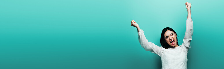 angry happy brunette asian woman yelling on turquoise background, panoramic shot