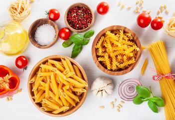 Fototapete - ingredients for italian cousine flat lay, pasta spaghetti penne fusilli tomato oil vegetables