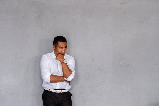 Young pensive mixed race businessman posing on a gray background thinking about something and looking to the side. Concept of problems in business and in personal life. Place for text
