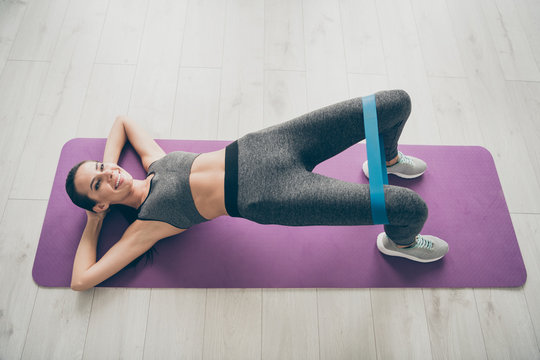 Top above high angle photo of joyful active sportive girl lie on purple mat practicing asana sport exercise make bridge raise knees with blue expander in house like fitness studio