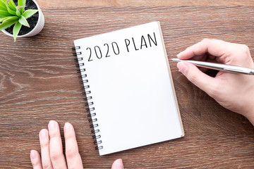 Wall Mural - Man hand is going to write 2020 plan and goals on notebook. Top view, flat lay.