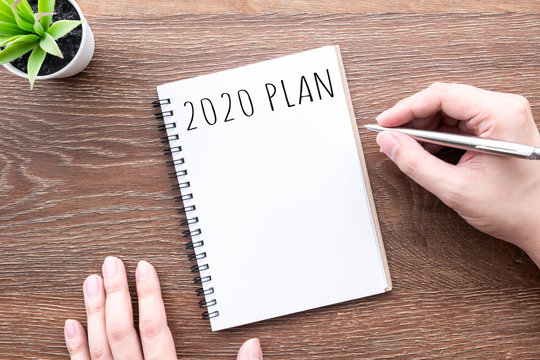 Man hand is going to write 2020 plan and goals on notebook. Top view, flat lay.