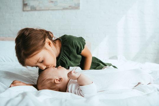 adorable child kissing little sister lying on white bedding