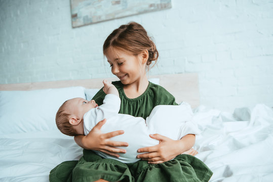 happy child holding cute little sister while sitting on white bedding