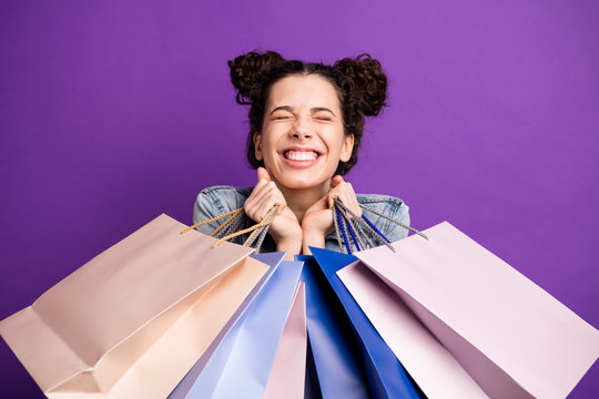 Close up photo of cheerful excited girl go shopping hold many bags feel dream dreamy enjoy her purchases wear denim jeans jacket outfit isolated over violet color background