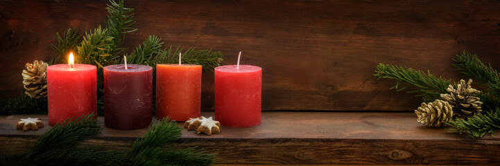First Advent, four red candles, one of them is burning, fir branches and Christmas decoration on dark rustic wood, wide panoramic format with copy space
